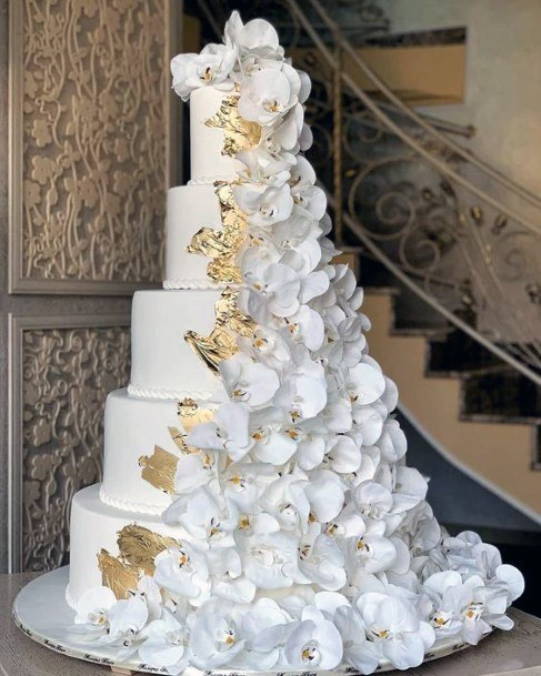 Fairy Tale Tall Tiered White Cake With Cascading White Florals And Gold Accents Design