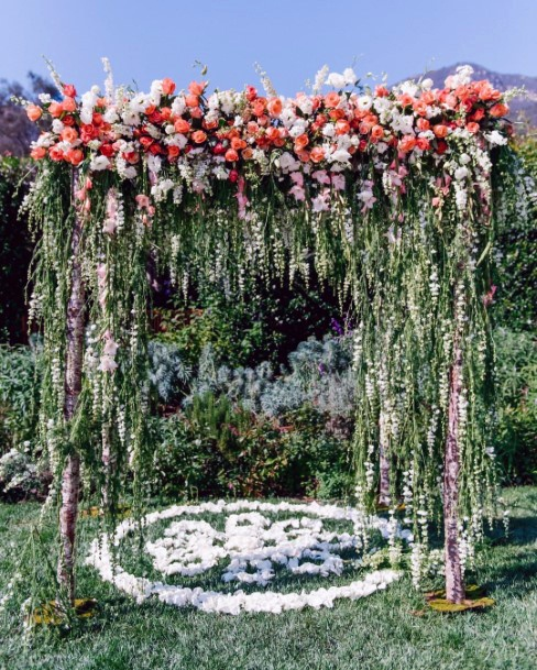 Fall Wedding Ideas Whimsical Orange And White Flowers With Hanging Greenery Wedding Arch