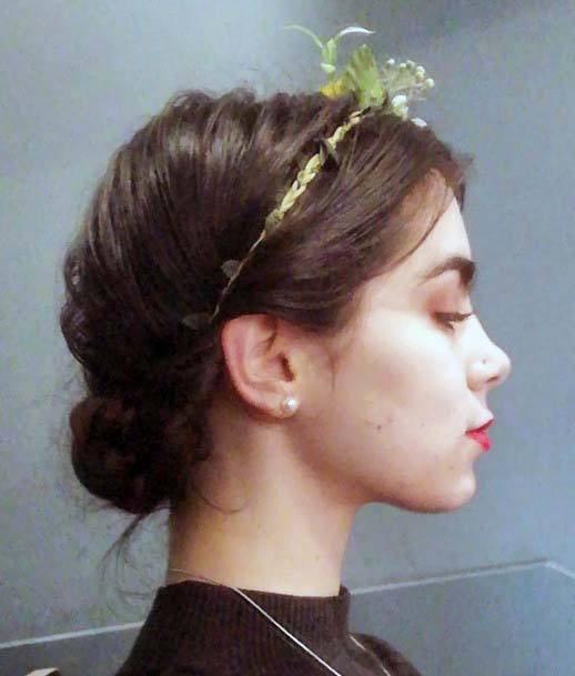 Female With Low Bun Hairstyle And Floral Hair Accessory