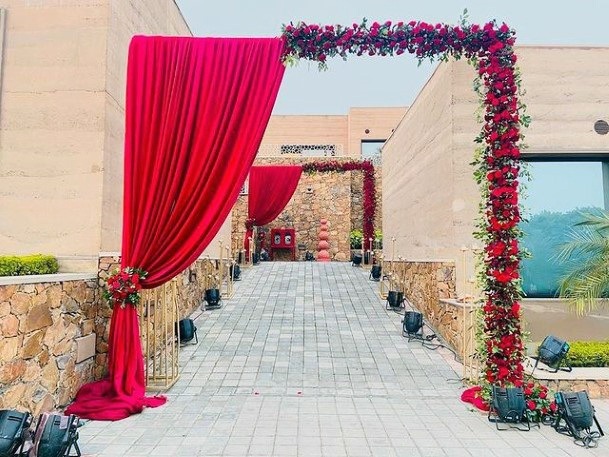 Red Curtains And Roses Welcome Angled Arch Indian Wedding Flowers